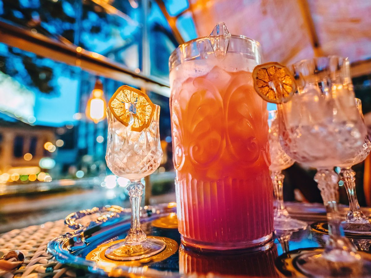 A small pitcher of the orange-pink drink, the Secret Garden, in between two empty glasses topped with dried orange slices.