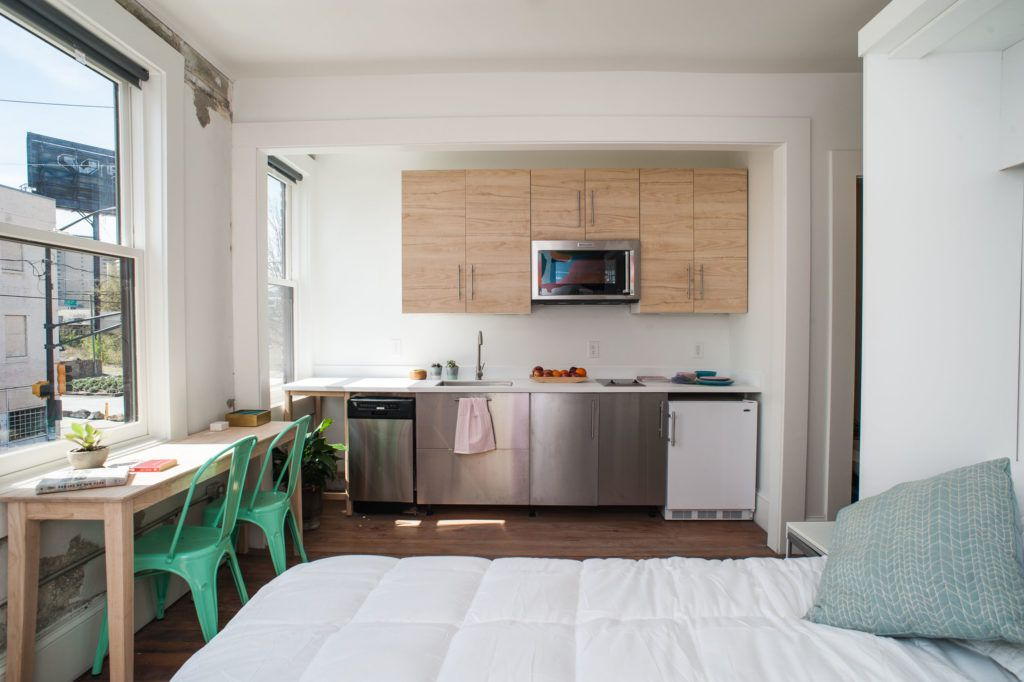 A studio apartment with bed and small kitchenette.