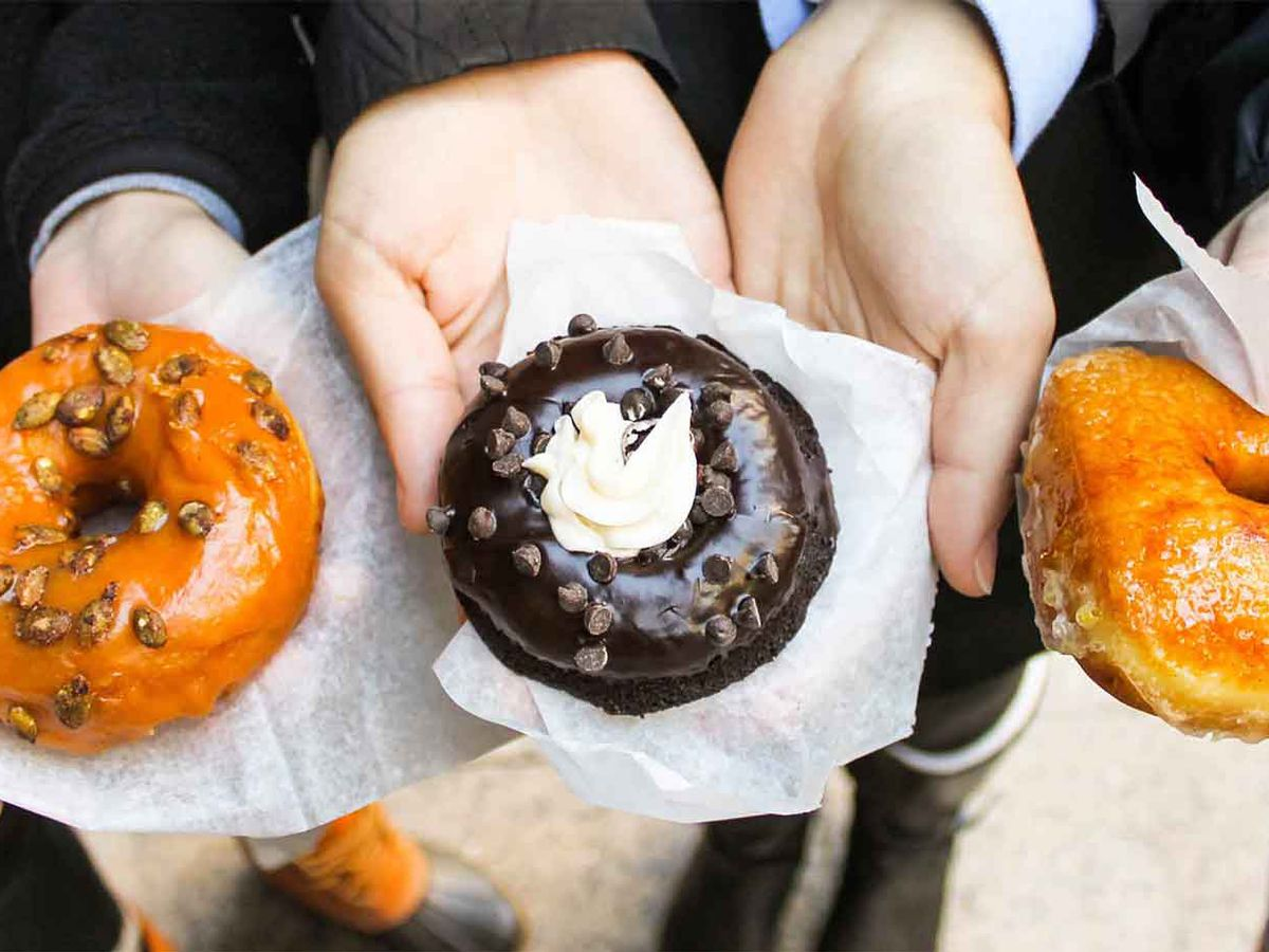 Hands outstretched offering three types of doughnuts, including a seasonal one to the left, a chocolate one in the middle and their creme brulee offering on the right.