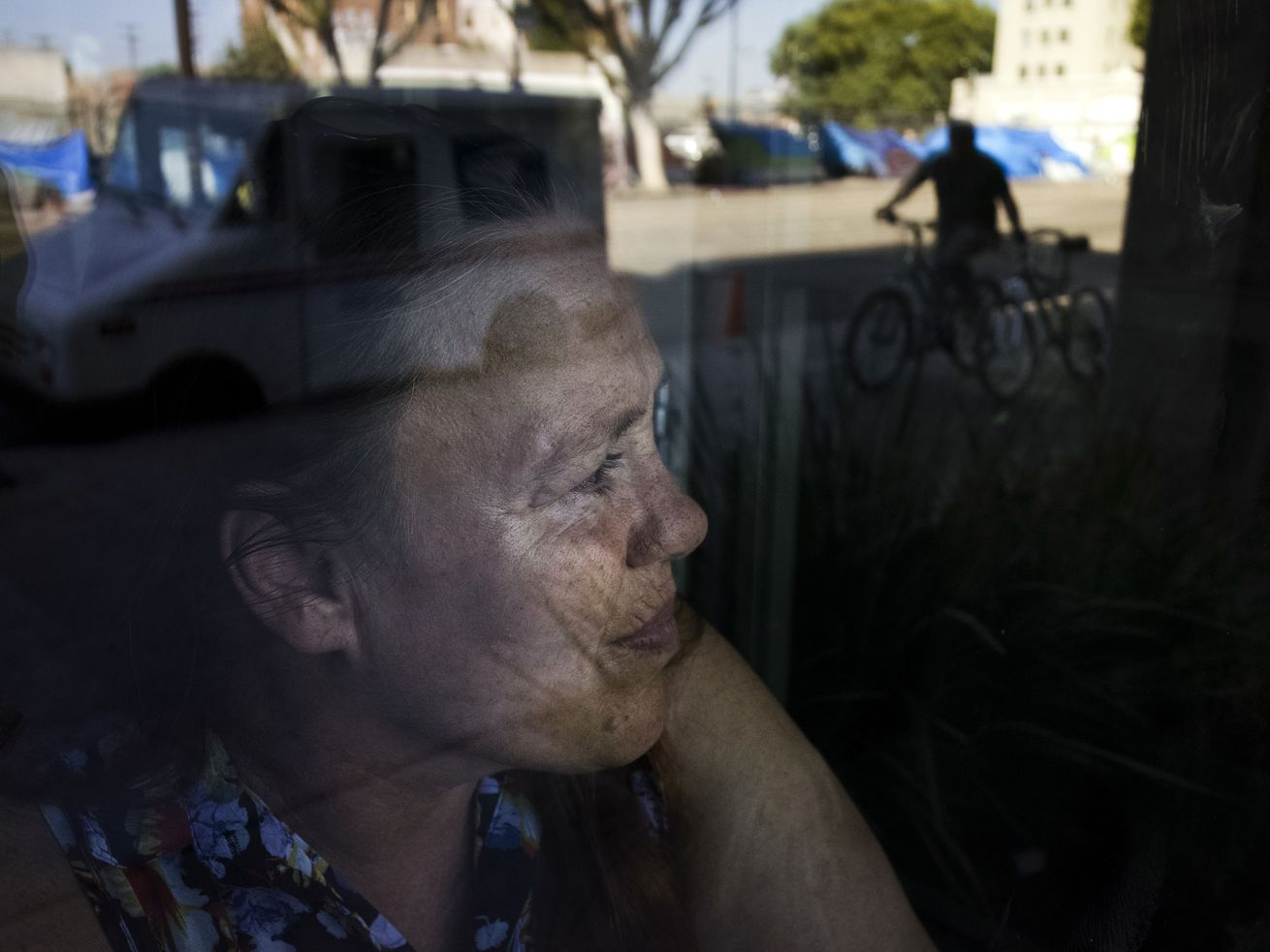 A person looking through a window on which is reflected an outdoor urban scene.