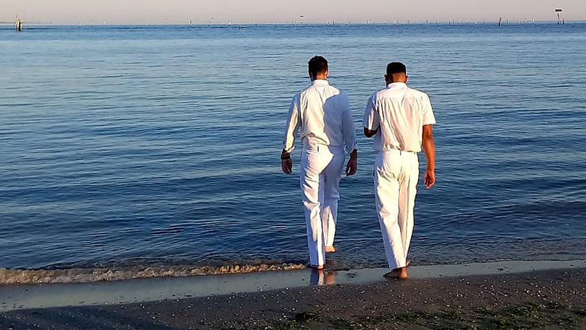 Elder Samuel Nagliati, a missionary for The Church of Jesus Christ of Latter-day Saints, left, walks into the Adriatic Sea with Lucky Ughulu to baptize him in Italy on Sunday, Sept. 12, 2021.