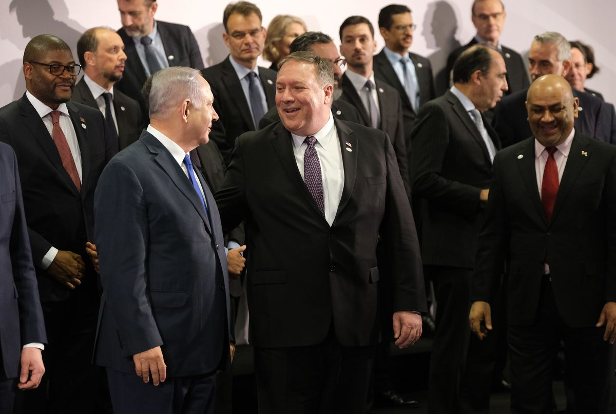 Secretary of State Mike Pompeo and Israeli Prime Minister Benjamin Netanyahu talk during the group photo at the Ministerial to Promote a Future of Peace and Security in the Middle East on February 14, 2019 in Warsaw, Poland.