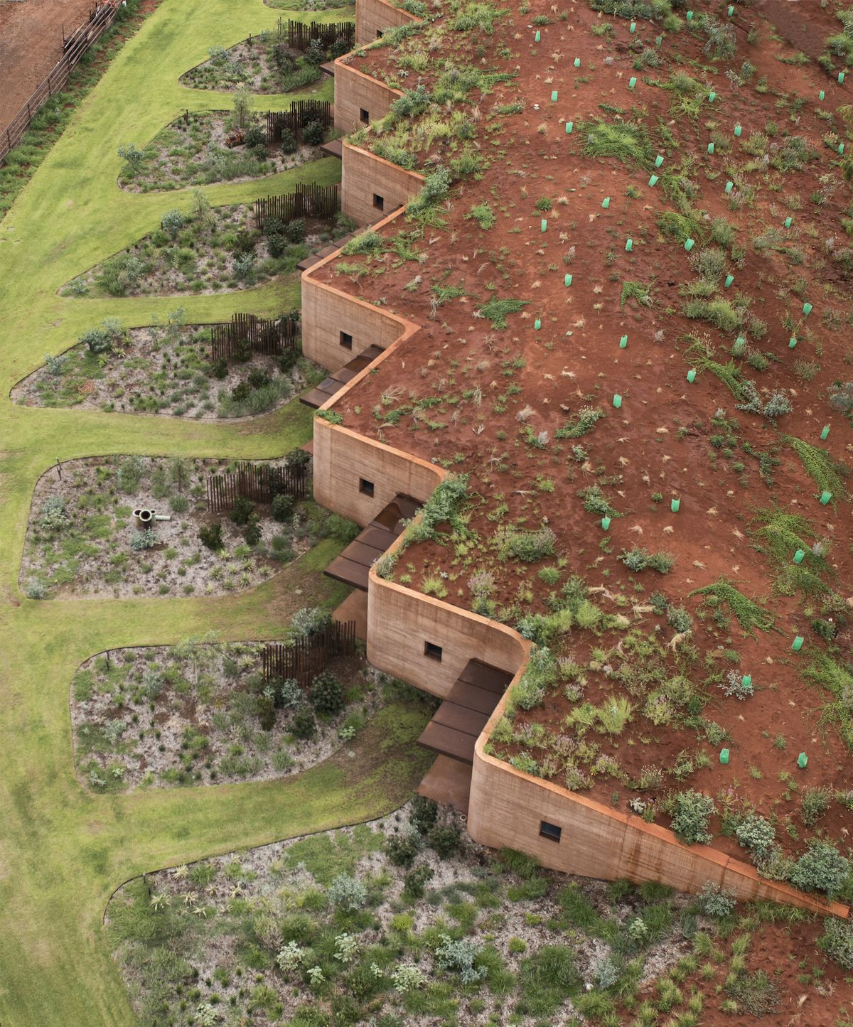 A zig-zagging wall made of red earth that's built into a hillside.