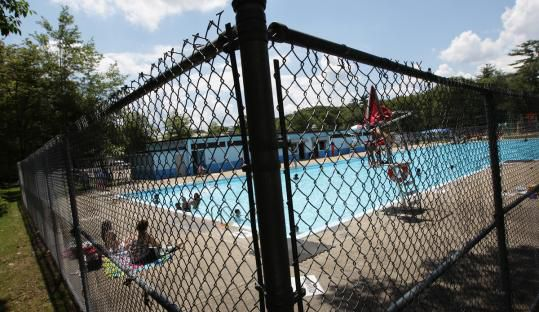 In the foreground is a fence. In the distance is an in-ground swimming pool.