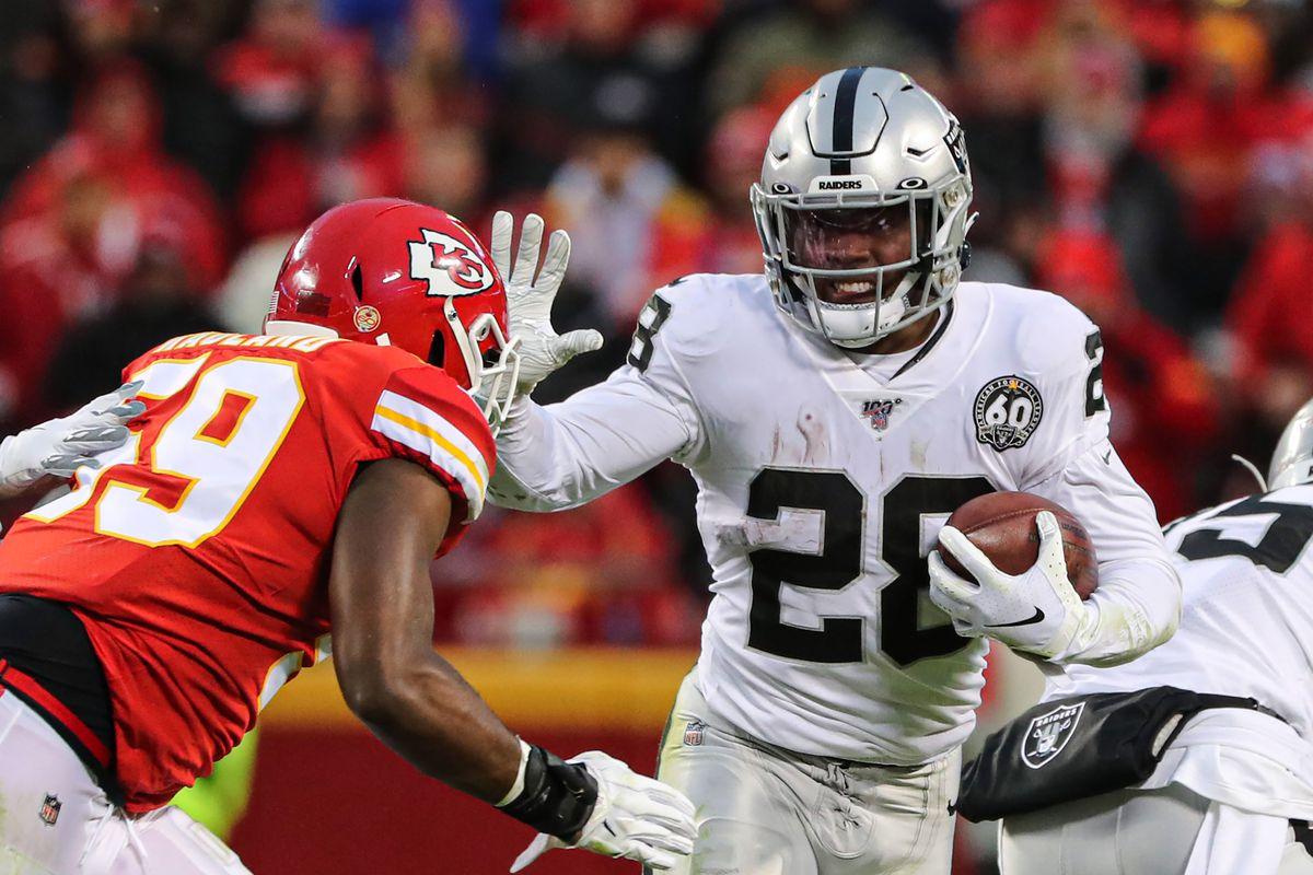 Oakland Raiders running back Josh Jacobs runs against Kansas City Chiefs inside linebacker Reggie Ragland during the first half at Arrowhead Stadium.