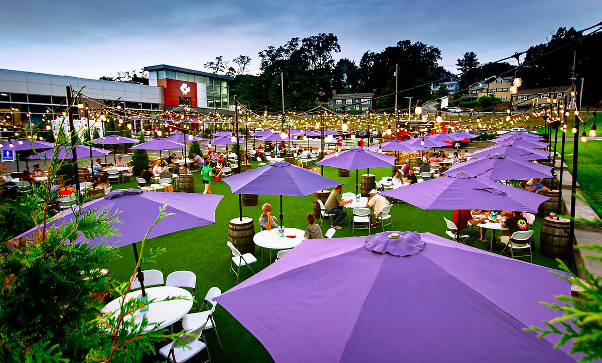 An expansive brewery patio features green turf and lavender umbrellas over round white tables