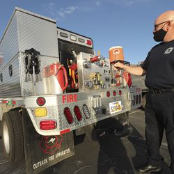 Orem firefighter Jason Earl looks over his wildfire brush truck as 41 firefighters from various Utah fire agencies gather in West Valley City on Wednesday, Sept. 9, 2020, before deploying to California to help in firefighting efforts there.