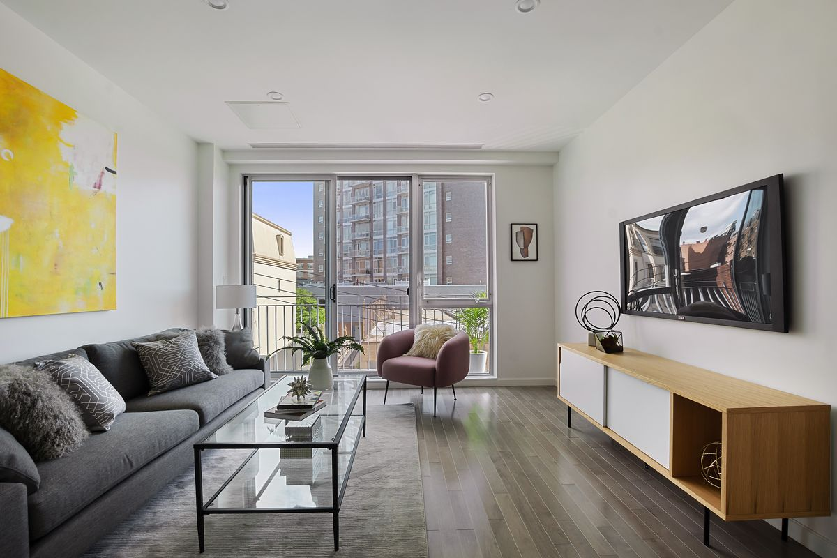 A living area with hardwood floors, a glass door that leads to a balcony, and a dark grey couch.