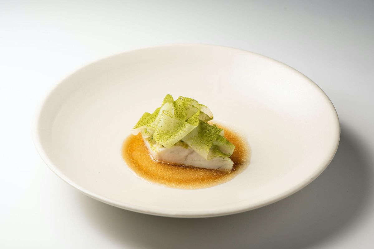 A tasting menu portion of steamed fish on a white plate.