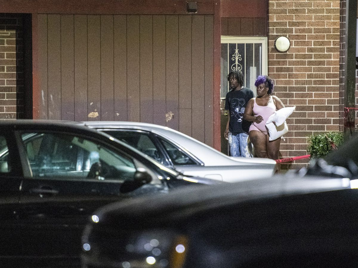 Residents look as police investigate the scene where multiple people were shot Sunday morning in the 7600 block of South Loomis. | Tyler LaRiviere/Sun-Times