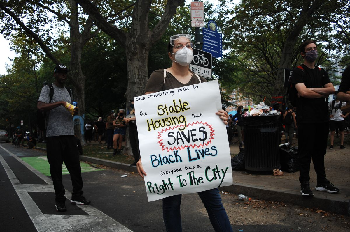 """A protester holds a sign that reads, """"Stop criminalizing paths to the stable housing that saves black lives. Everyone has a right to the city."""""""