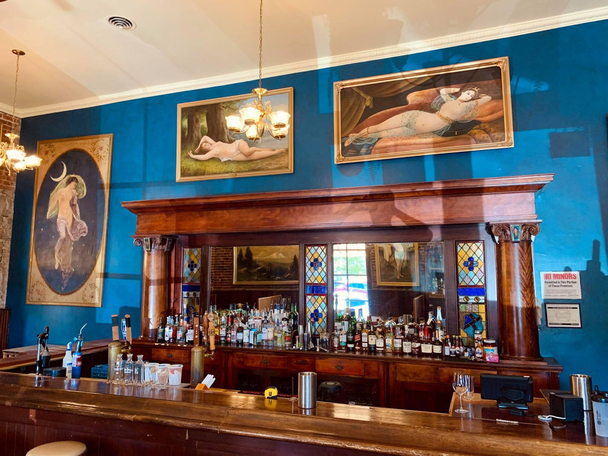 A blue bar with paintings and a mahogany bar at the Baldwin Saloon in the Dalles