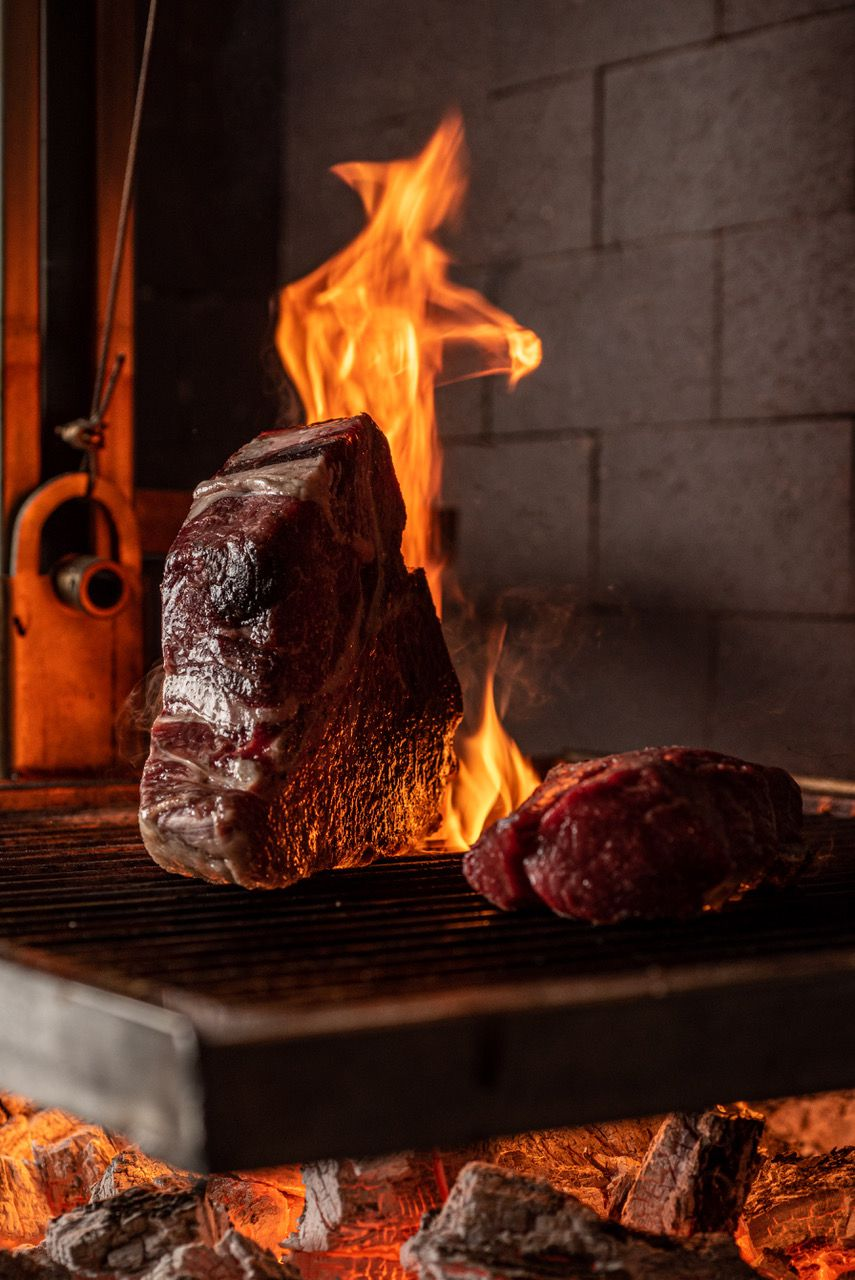 Large format steaks at Fia Steak over flaming wooden grill.