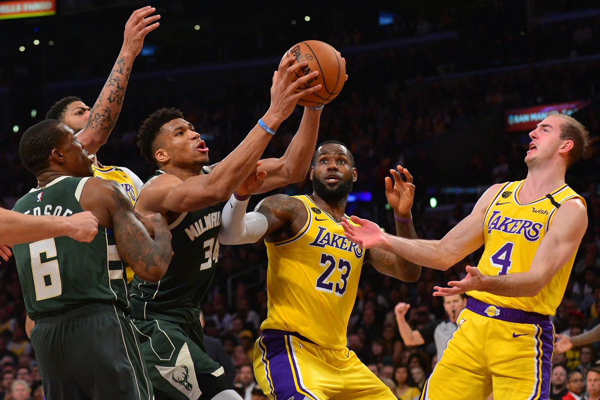 Milwaukee Bucks forward Giannis Antetokounmpo grabs a rebound against Los Angeles Lakers forward LeBron James and guard Alex Caruso during the second half at Staples Center.