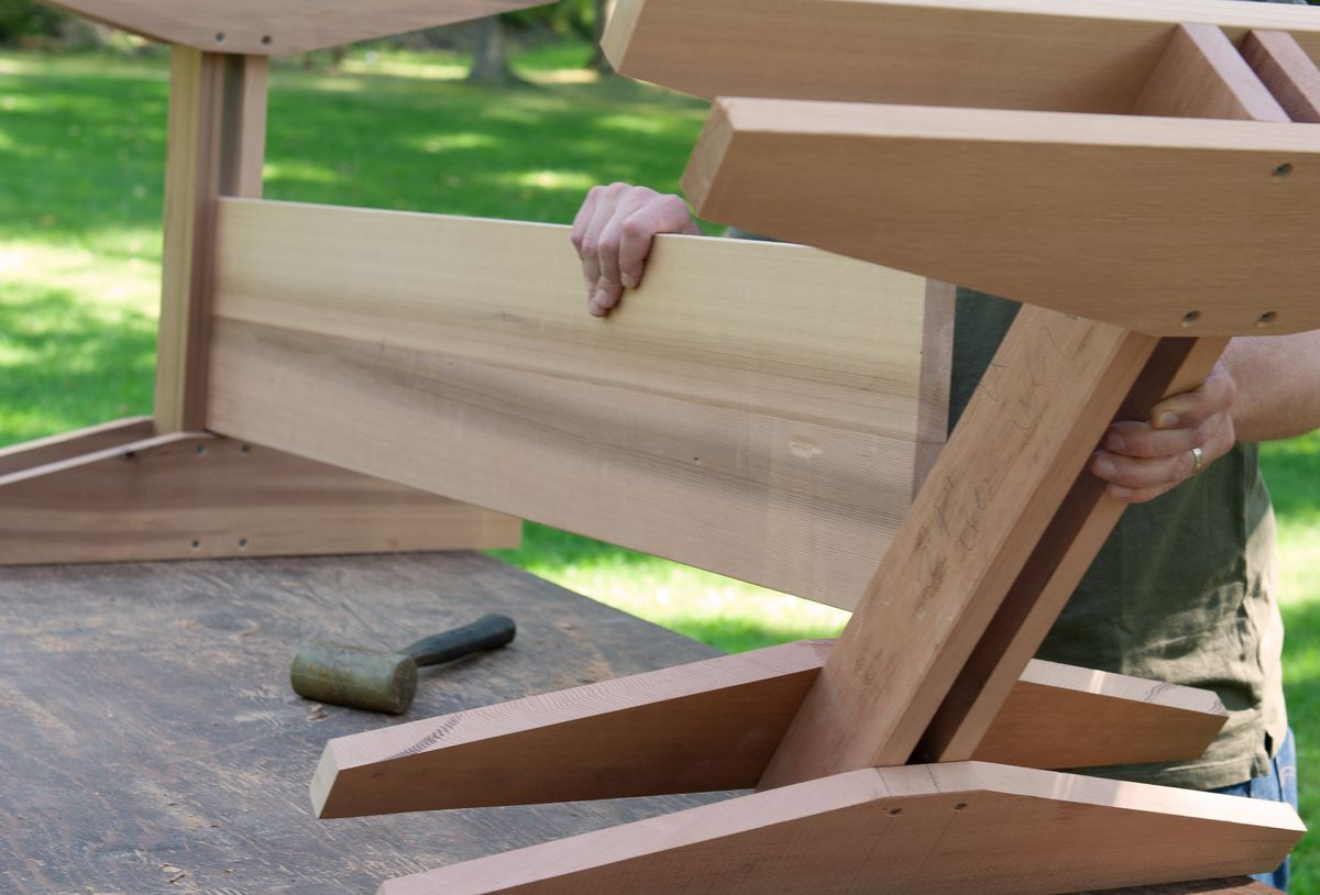 Man Joins Leg Assemblies Of Picnic Table