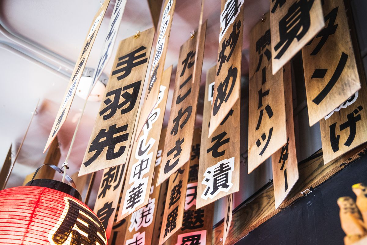 Thin strips of wood painted with Japanese characters hang from the ceiling.