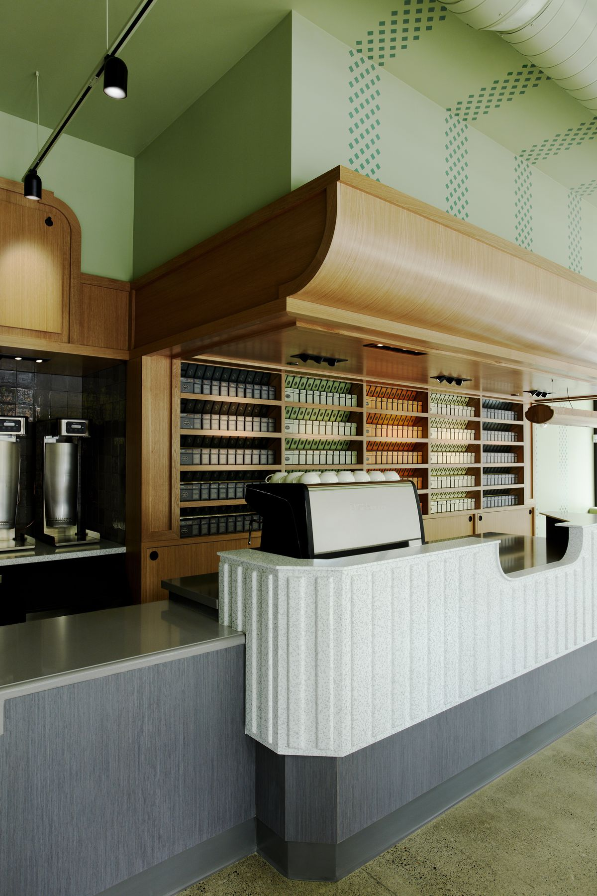 A white counter houses an expresso machine, with boxes of Steven Smith teas in the back.