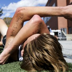 """""""For My Family"""" is written on the arm of Morgan High School runner Parker Wallace as he lays on the ground after finishing in 26th in the 3A Boys State Cross-Country Championships at Highland High School in Salt Lake City on Wednesday, Oct. 23, 2019."""