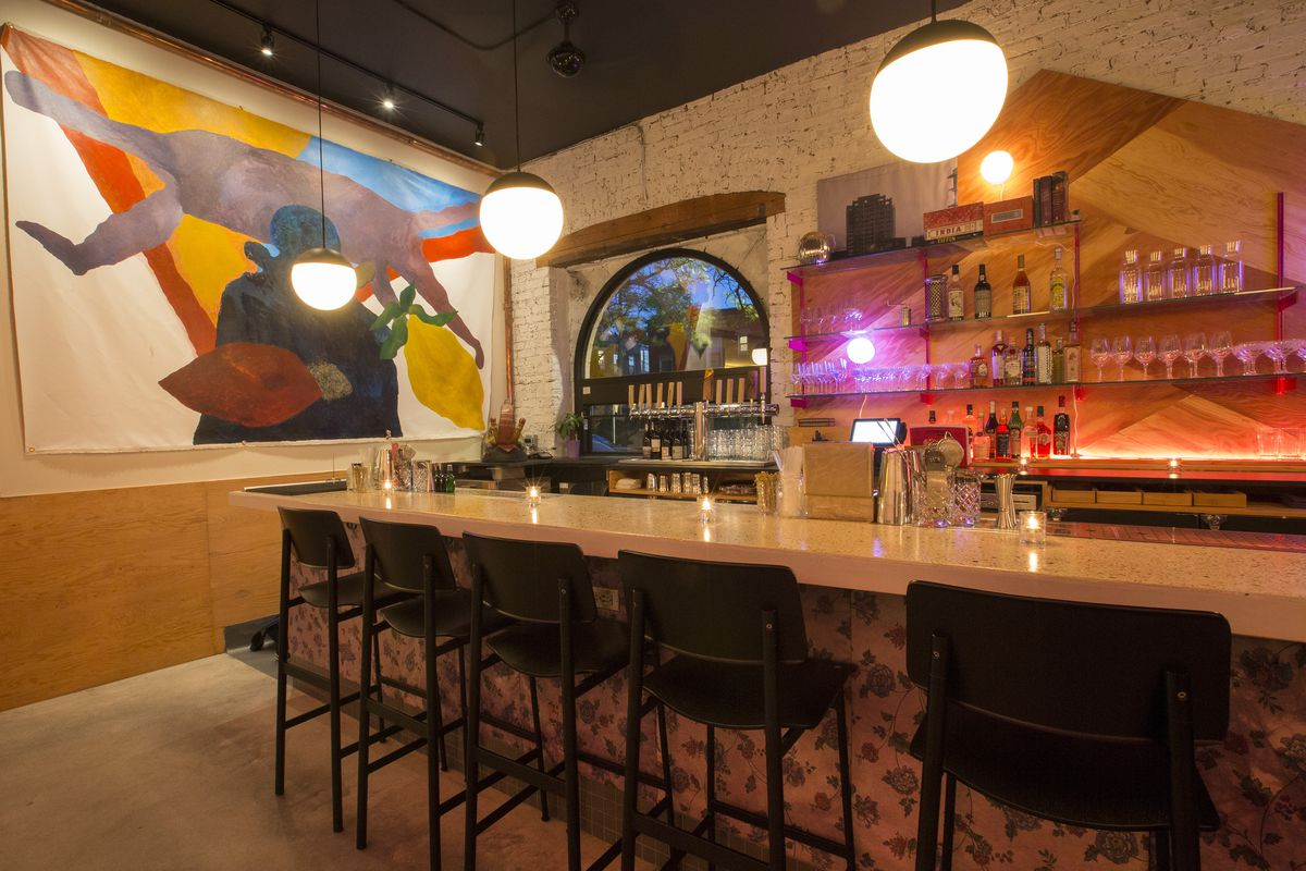 A photo of a long bar with black chairs.