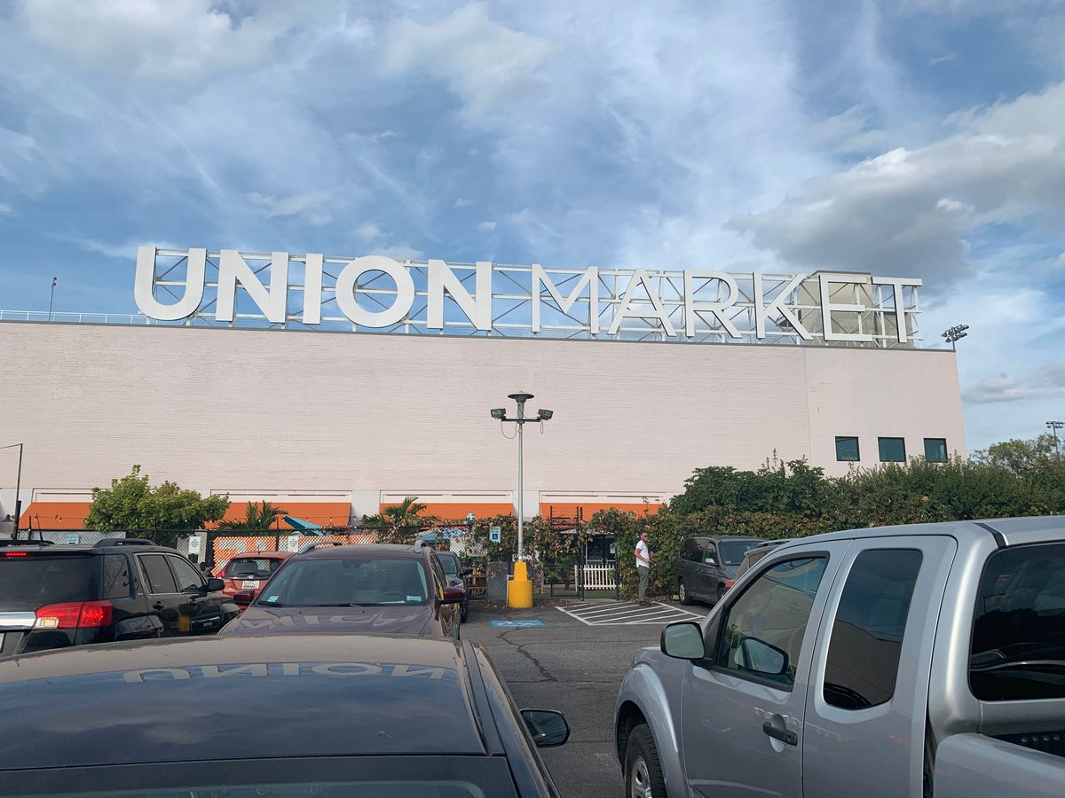 """An old market building with a large sign on top that says """"Union Market."""" There is a parking lot outside."""