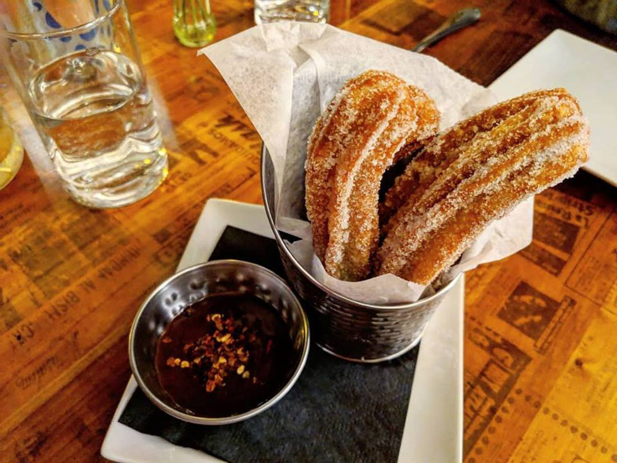 Churros stick out of a metal pail lined with paper, alongside a spicy chocolate dipping sauce, at Gustazo in Cambridge