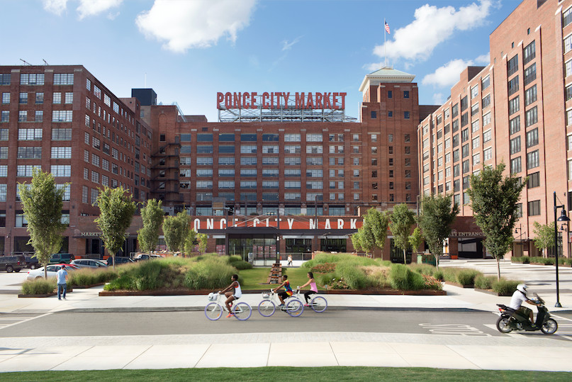 In the foreground is a street where there are people riding bicycles. In the distance is a group of buildings with red brick facades. On top of one of the buildings is a sign with words that read: Ponce City Market.