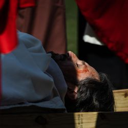Isaac Bucio, who plays Jesus Christ, acts as if he is dead during Via Crucis, or the Way of the Cross, on the field of St. Procopius Catholic Church in Pilsen, Friday morning, April 2, 2021. The annual Via Crucis is a Good Friday tradition that reenacts the Stations of the Cross, a Catholic devotion that recounts Jesus' passion and death.
