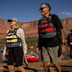 Ann Romney, left, and her husband, Sen. Mitt Romney, R-Utah, walk up on shore while rafting a section of the Colorado River northeast of Moab on Saturday, Sept. 18, 2021.