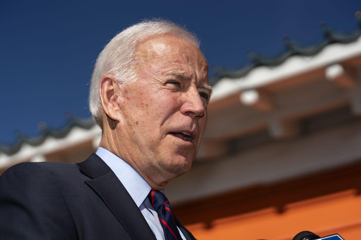 Biden speaks under the California sun in front of a bright orange building.