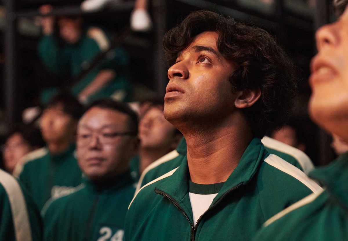 Pakistani Squid Game player Ali looks up soulfully from a group of contestants
