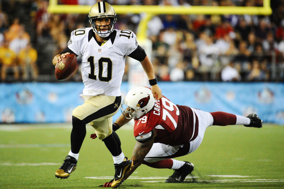Aug 5, 2012; Canton, OH, USA; New Orleans Saints quarterback Chase Daniel (10) gets away from Arizona Cardinals defensive end David Carter (79) during the first half of a preseason game at Fawcett Stadium. Mandatory Credit: Tim Fuller-US PRESSWIRE