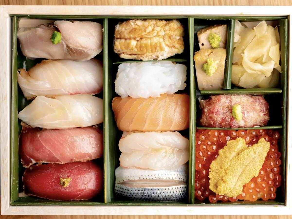 A top-down view of a wooden box filled with various nigiri and other sushi selections