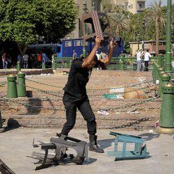 An Egyptian riot policeman smashes plastic chairs as police clear Tahrir Square in Cairo, Egypt, Saturday, Sept. 15, 2012 after days of protests near the U.S. embassy over a film insulting Prophet Muhammad.