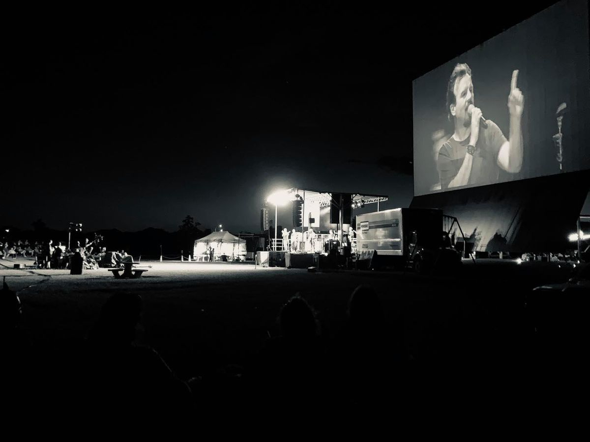 a black and white image of a large drive-in theater screen. In the background there are tents and people sitting at picnic benches. On the screen is a man holding a microphone.