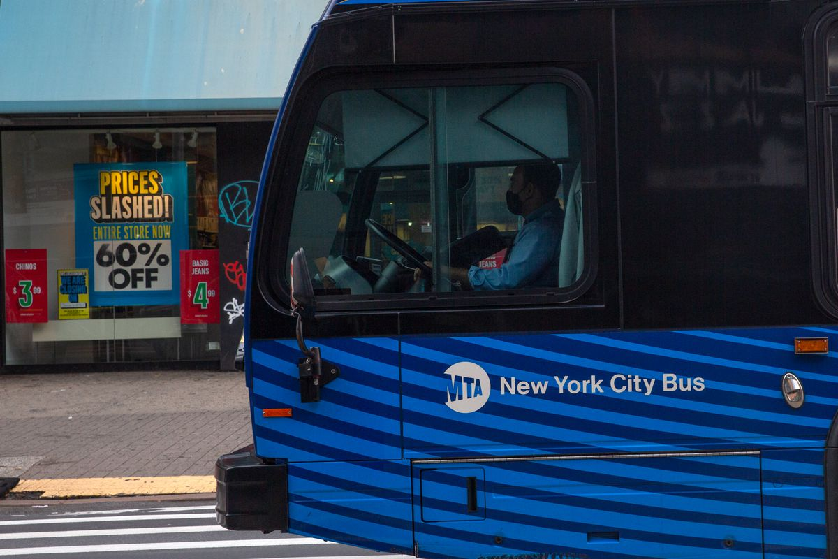 An MTA bus heads past signs of struggling businesses along Harlem's 125th Street, Dec. 1, 2020.