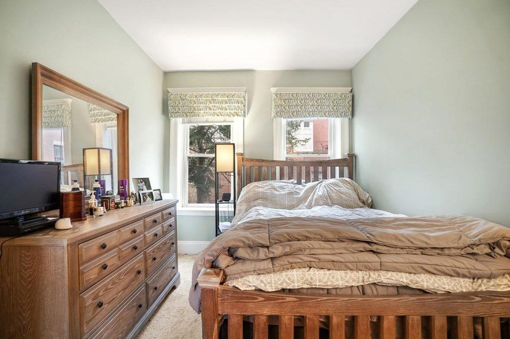A bedroom with a bed alongside a dresser.