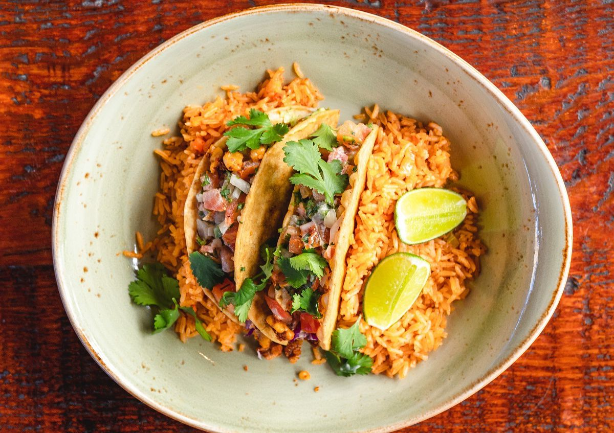 Tacos, salsa, and rice and beans on a plate at Backyard Kitchen & Tap in San Diego.