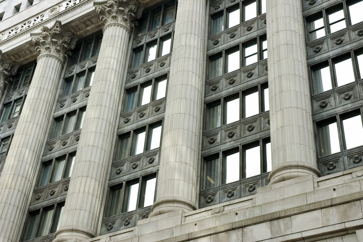 The exterior of a Classical Revival Style building with vertical greek columns topped by Corinthian capitals.