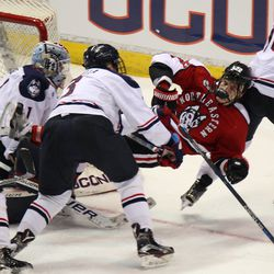 UConn's Ryan Segalla (3) sends Northeastern's Tanner Pond (22) flying after a check.