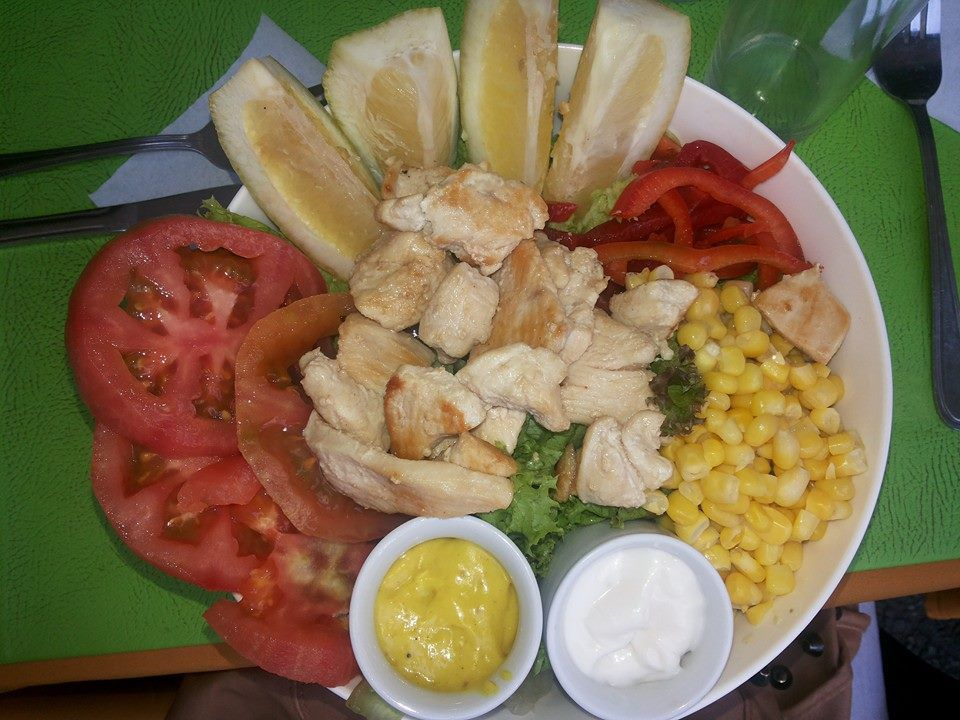 From above, slices of chicken in the center of a plate surrounded by slices of tomato, corn, peppers, lemon, and sauces