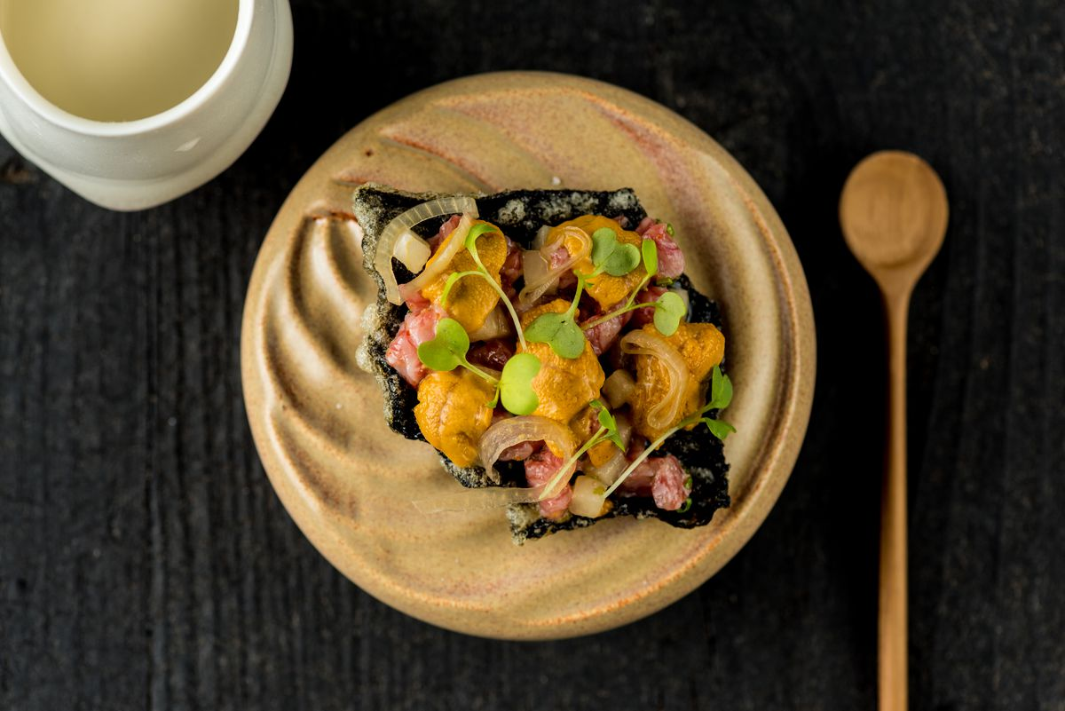 A fried nori chip topped with A5 beef tartare, Fort Bragg uni, pickled shallots, micro wasabi, Asian pear, and togarashi