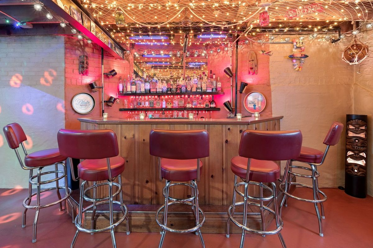 A basement bar with five stools, woven netting and string light decor.