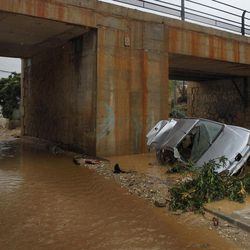 Residents walk by a wrecked car carried away by flash floods after heavy rain in the town of Villanueva del Rosario, Malaga, southern Spain, Friday, Sept. 28, 2012. Homes were destroyed and at least one woman was killed. Rescue workers are searching to determine if there are more victims.