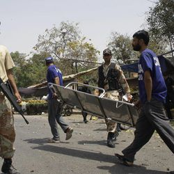 Pakistani security officials secure the area of a suicide attack in Karachi, Pakistan on Thursday, April 5, 2012. Police say a suspected suicide bomber detonated explosives near a vehicle carrying a senior police official in the southern Pakistani city of Karachi, killing two people. (AP Photo)