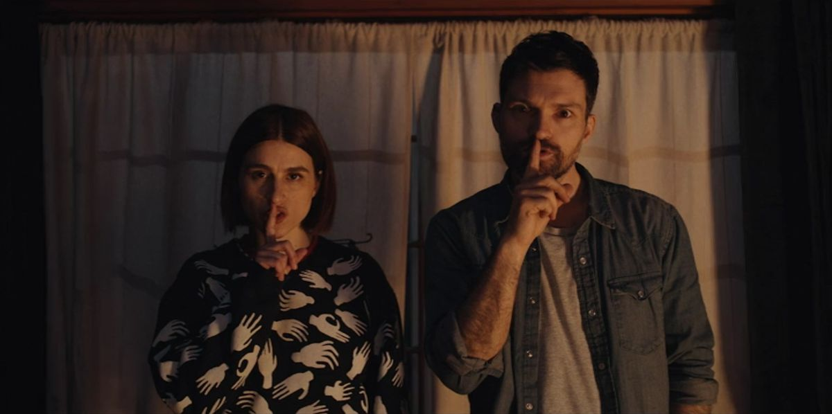 A still from Scare Me showing Josh Reuben and Aya Cash shushing the viewer