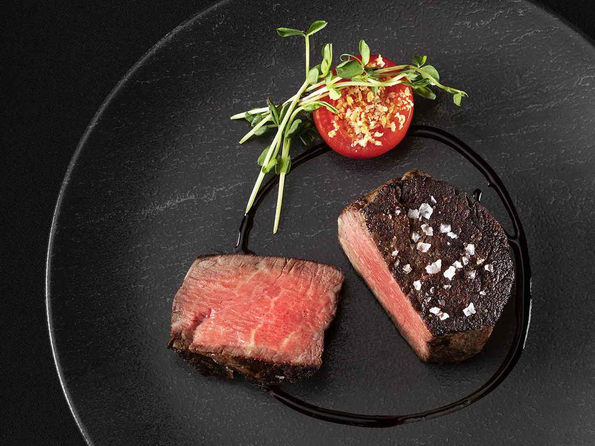 A filet mignon on a black plate with a tomato