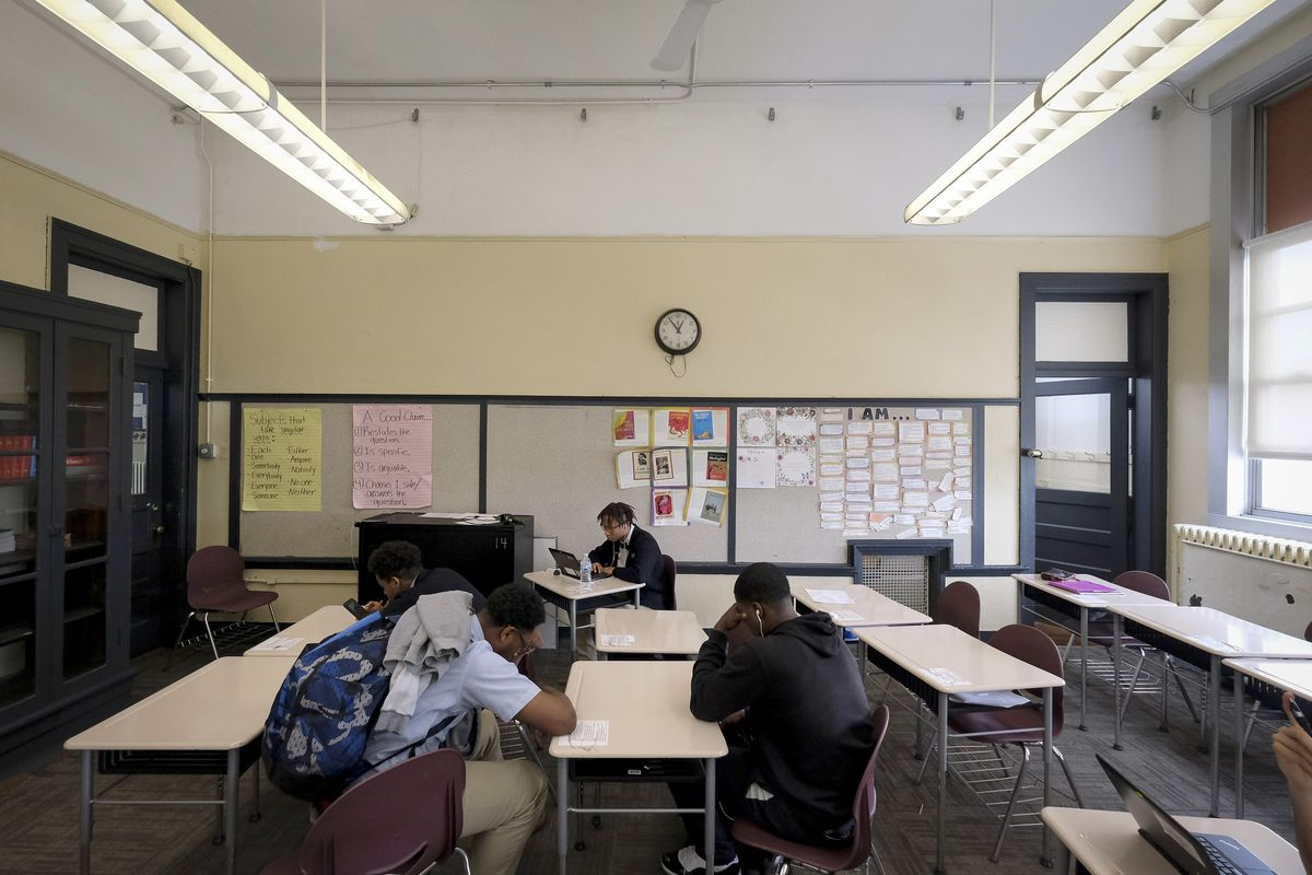 Four or five male students sit looking down in a classroom
