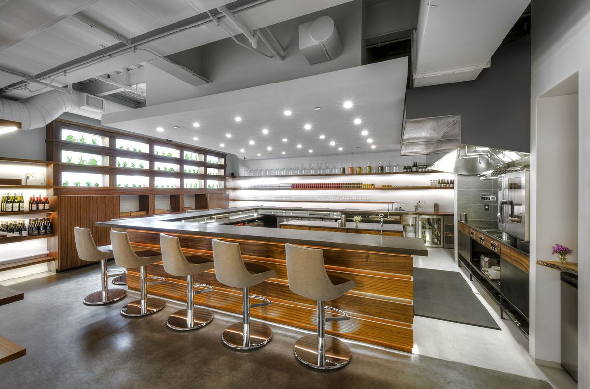 A minimalist, bright white restaurant interior featuring a high-end tasting counter