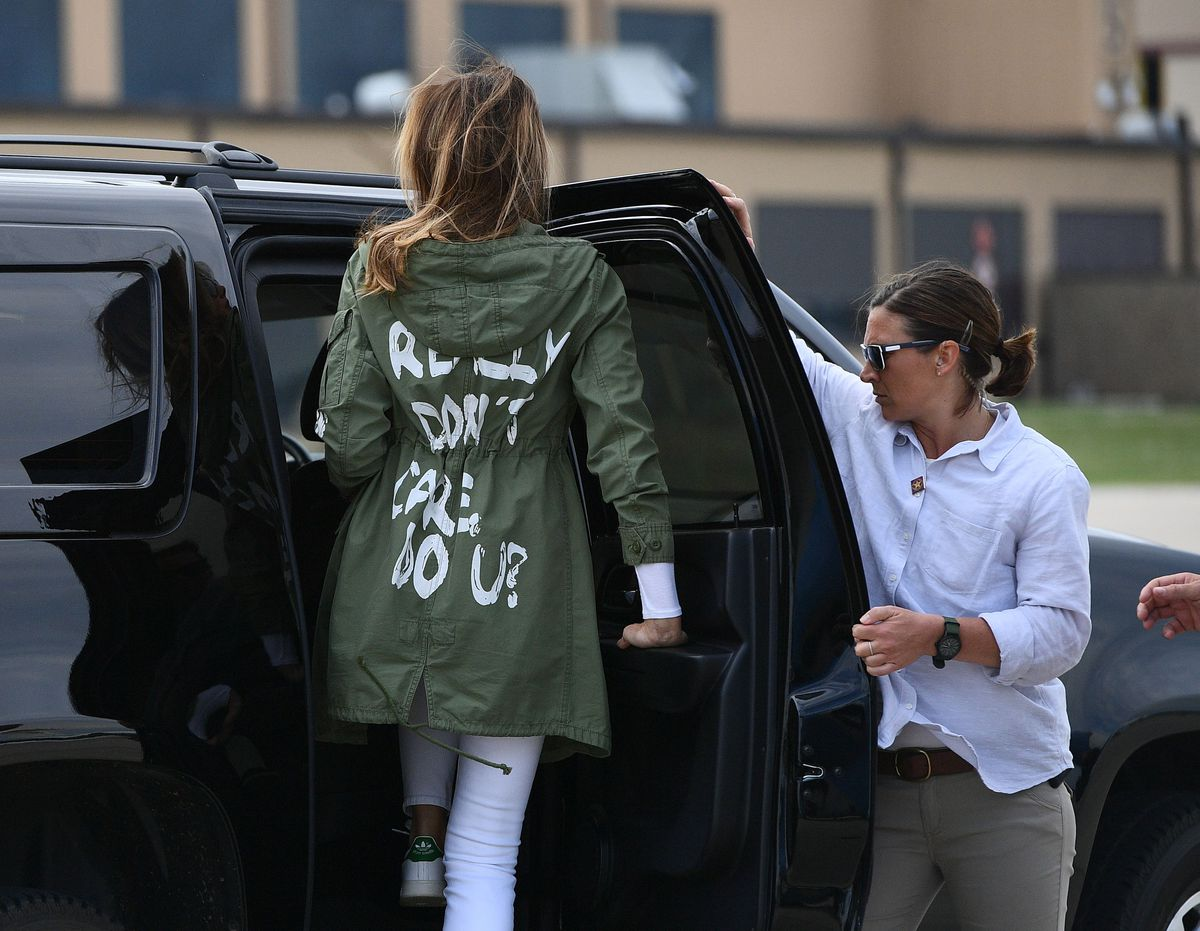 Melania Trump gets into a car, exposing the back of her jacket.