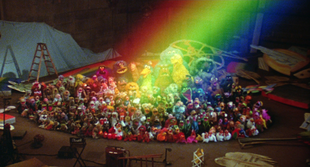 The Muppets underneath a rainbow.
